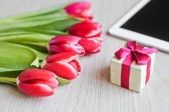 Κόκκινες τουλίπες, κιβώτιο δώρων με ένα κόκκινο τόξο και ταμπλέτα Στοκ φωτογραφία με δικαίωμα ελεύθερης χρήσης