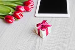 Κόκκινες τουλίπες, κιβώτιο δώρων με ένα κόκκινο τόξο και ταμπλέτα Στοκ Εικόνα