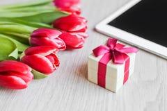Κόκκινες τουλίπες, κιβώτιο δώρων με ένα κόκκινο τόξο και ταμπλέτα Στοκ εικόνα με δικαίωμα ελεύθερης χρήσης