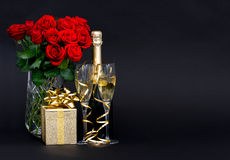 Κόκκινες τριαντάφυλλα και σαμπάνια με τη χρυσή διακόσμηση Στοκ εικόνα με δικαίωμα ελεύθερης χρήσης