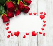 Κόκκινες τριαντάφυλλα και ευχετήρια κάρτα Στοκ Εικόνα
