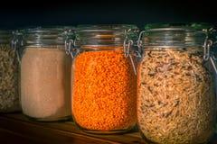 Κόκκινες φακές και άγριο ρύζι στα βάζα μεταξύ των ξηρών αγαθών σε ένα οψοφυλάκιο κουζινών στοκ εικόνες