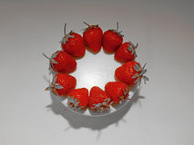 Κόκκινες φράουλες στον άσπρο στρογγυλό πυροβολισμό στούντιο πιάτων Στοκ Φωτογραφία