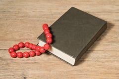 Κόκκινες χάντρες στο καφετί βιβλίο Στοκ φωτογραφία με δικαίωμα ελεύθερης χρήσης