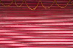 Κόκκινες χρωματισμένες ζαρωμένες πόρτα μετάλλων και γιρλάντα λουλουδιών Στοκ Φωτογραφία