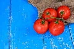 κόκκινες juicy ντομάτες στον μπλε ξύλινο πίνακα, οριζόντιο Στοκ Εικόνες