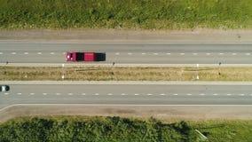 Κόκκινες tipper και κίνηση αυτοκινήτων κατά μήκος της σύγχρονης τοπ άποψης εθνικών οδών απόθεμα βίντεο