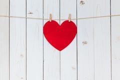 Κόκκινη ένωση καρδιών στη σκοινί για άπλωμα στο ξύλινο άσπρο υπόβαθρο με το s Στοκ φωτογραφίες με δικαίωμα ελεύθερης χρήσης