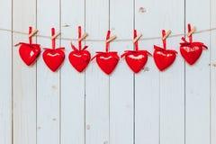 Κόκκινη ένωση καρδιών στη σκοινί για άπλωμα στο ξύλινο άσπρο υπόβαθρο με το s Στοκ Εικόνες