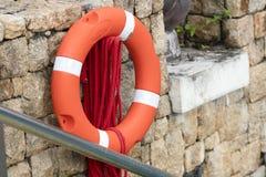 Κόκκινη ένωση σημαντήρων ζωής στον τοίχο πετρών για τη βοήθεια των ανθρώπων σε ένα ατύχημα νερού Στοκ φωτογραφία με δικαίωμα ελεύθερης χρήσης