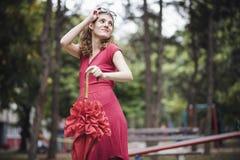 Κόκκινη αναδρομική γυναίκα με την κόκκινη ομπρέλα Στοκ Φωτογραφία