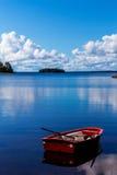 Κόκκινη βάρκα κωπηλασίας προς τον ειδυλλιακό κόλπο στοκ φωτογραφία