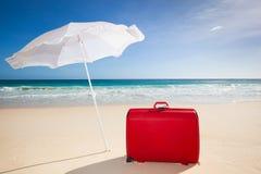 Κόκκινη βαλίτσα κάτω από άσπρο sunshade Στοκ Φωτογραφία