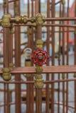 Κόκκινη βαλβίδα στην κατασκευή σωλήνων χαλκού σε υπαίθριο Στοκ Εικόνες