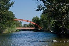 Κόκκινη γέφυρα που επεκτείνεται πέρα από τον ποταμό Στοκ Εικόνες