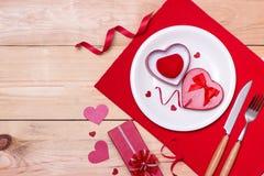Κόκκινη γαμήλια διακόσμηση με τα δαχτυλίδια και τα τριαντάφυλλα στοκ εικόνες