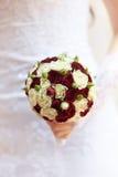 Κόκκινη γαμήλια ανθοδέσμη με τα τριαντάφυλλα στα χέρια Στοκ εικόνα με δικαίωμα ελεύθερης χρήσης
