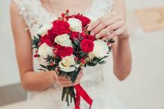 Κόκκινη γαμήλια ανθοδέσμη στα χέρια της κινηματογράφησης σε πρώτο πλάνο νυφών Στοκ Φωτογραφία