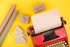 Κόκκινη γραφομηχανή έννοιας διακοπών με το κενό έγγραφο τεχνών, τα κιβώτια δώρων και το τυλίγοντας έγγραφο για το κίτρινο υπόβαθρ Στοκ φωτογραφία με δικαίωμα ελεύθερης χρήσης