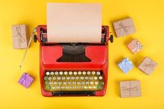 Κόκκινη γραφομηχανή έννοιας διακοπών με το κενό έγγραφο τεχνών, κιβώτια δώρων για το κίτρινο υπόβαθρο Στοκ Εικόνα