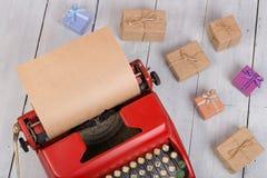 κόκκινη γραφομηχανή με το κενό έγγραφο τεχνών, κιβώτια δώρων για το άσπρο ξύλινο υπόβαθρο Στοκ φωτογραφία με δικαίωμα ελεύθερης χρήσης