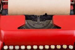 Κόκκινη γραφομηχανή με το κενό φύλλο εγγράφου κλείστε επάνω Στοκ Φωτογραφίες