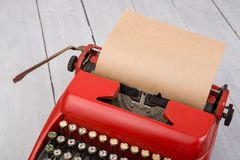 Κόκκινη γραφομηχανή με το κενό φύλλο εγγράφου στον άσπρο ξύλινο πίνακα Στοκ εικόνα με δικαίωμα ελεύθερης χρήσης