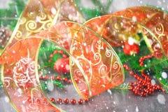 Κόκκινη διακοσμητική κορδέλλα Χριστουγέννων από το organza που περιβάλλεται από τους κλάδους έλατου Στοκ Φωτογραφίες