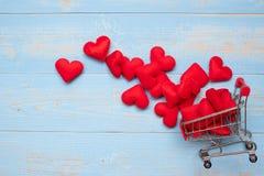 Κόκκινη διακόσμηση μορφής καρδιών τοπ άποψης με το μίνι κάρρο αγορών στο μπλε ξύλινο επιτραπέζιο υπόβαθρο αγάπη, ρομαντικός, που  στοκ φωτογραφία