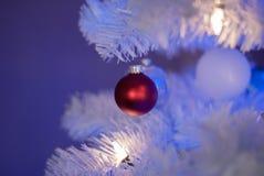 Κόκκινη διακόσμηση σε ένα άσπρο χριστουγεννιάτικο δέντρο με τα άσπρα και μπλε φω'τα στοκ φωτογραφία με δικαίωμα ελεύθερης χρήσης