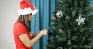 Κόκκινη εξάρτηση Χριστουγέννων των μπλουζών και των καπέλων στο brunette απόθεμα βίντεο