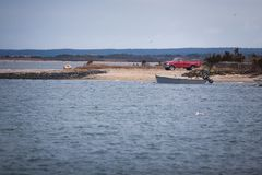 Κόκκινη επανάλειψη σε μια ακτή με μια βάρκα Στοκ φωτογραφίες με δικαίωμα ελεύθερης χρήσης