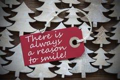 Κόκκινη ετικέτα Χριστουγέννων με πάντα το λόγο να χαμογελάσει στοκ φωτογραφίες