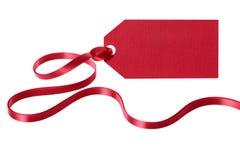 Κόκκινη ετικέττα δώρων με τη μακριά σγουρή κορδέλλα που απομονώνεται στο άσπρο υπόβαθρο Στοκ Εικόνες