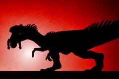 Κόκκινη ελαφριά σκιά σημείων του allosaurus που δαγκώνει ένα σώμα στον τοίχο Στοκ φωτογραφία με δικαίωμα ελεύθερης χρήσης