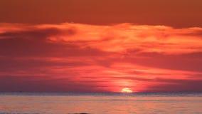 Κόκκινη ηλιοβασιλέματος αντανάκλαση φωτός του ήλιου οριζόντων ήλιων μισή πίσω στη θάλασσα φιλμ μικρού μήκους