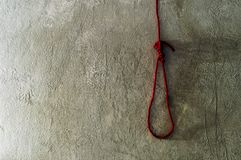 Κόκκινη θηλιά σχοινιών για το θάνατο στον τοίχο τσιμέντου Στοκ Φωτογραφία