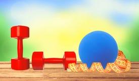 Κόκκινη ικανότητα αλτήρων, ταινία μέτρου και μπλε σφαίρα στο ξύλινο tabl Στοκ Εικόνες