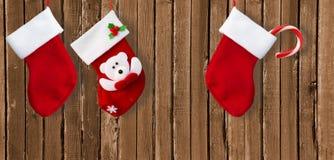 Κόκκινη κάλτσα Χριστουγέννων στον καφετή ξύλινο τοίχο Στοκ Φωτογραφίες