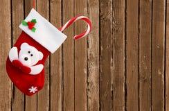 Κόκκινη κάλτσα Χριστουγέννων στον καφετή ξύλινο τοίχο Στοκ Εικόνα