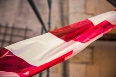 Κόκκινη και άσπρη κορδέλλα για τα κτήρια Χωρισμός των ζωνών ασφάλειας στοκ φωτογραφία