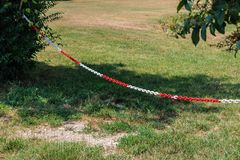 Κόκκινη και άσπρη πλαστική αλυσίδα που απαγορεύει τη μετάβαση/το χώρο στάθμευσης, που κρεμά σε δύο θάμνους στοκ φωτογραφία