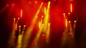 Κόκκινη και κίτρινη λάμψη επικέντρων στην ομίχλη σε μια συναυλία βράχου στο σκοτάδι απόθεμα βίντεο