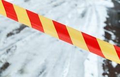 Κόκκινη και κίτρινη ριγωτή ταινία στο χειμερινό δρόμο Στοκ εικόνα με δικαίωμα ελεύθερης χρήσης