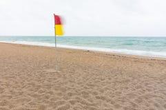 Κόκκινη και κίτρινη σημαία προειδοποίησης σε μια εγκαταλειμμένη παραλία στοκ εικόνες