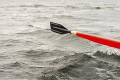Κόκκινη και μαύρη ξύλινη βάρκα κωπηλασίας κουπιών στη λίμνη στοκ φωτογραφία με δικαίωμα ελεύθερης χρήσης
