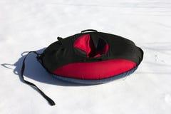 Κόκκινη και μαύρη υλική εσωτερική σωλήνωση χιονιού στο λευκό Στοκ εικόνα με δικαίωμα ελεύθερης χρήσης