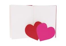 Κόκκινη και ρόδινη καρδιά εγγράφου στο κενό ανοικτό βιβλίο που απομονώνεται στο λευκό στοκ εικόνες