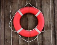 Κόκκινη και στρογγυλή lifebuoy ένωση στον καφετή ξύλινο τοίχο στοκ εικόνες με δικαίωμα ελεύθερης χρήσης