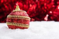 Κόκκινη και χρυσή σφαίρα Χριστουγέννων στο χιόνι με tinsel, υπόβαθρο Χριστουγέννων Στοκ Εικόνες